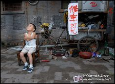 Photograph of Little Chinese boy sitting in the streets of Beijing Hutong, Source: Frantisek Staud