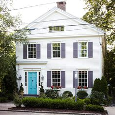 Eye-Catching Color Combos. Bright colors make this traditional facade stand out. The front door is painted three different shades of blue-green, with areas sanded off between layers and a stain added for depth. The contrast between the door and purple shutters with the clean white siding makes the house intriguing and eludes to even more color combinations inside.