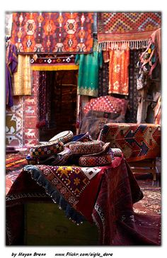 Carpets layed out on the sand next to camels to create Moroccan bed canopy luxury
