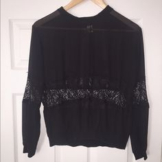 H&M Divided Sheer Black Lace Blouse This shirt is in PERFECT condition! Bought a couple years ago and wore this only ONCE for a concert. Other than that, it has been sitting around for a while! It is a sheer black long sleeve blouse with lace paneling the front mid-section, as well as the mid-section of the arms. Size is a US 4. Such a gorgeous top! H&M Tops Blouses