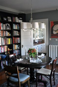I love this- a round dining room table with bookshelves on the wall, this way with a switch of a few chairs, it can be a great library reading space or a dining room when you have guests over.