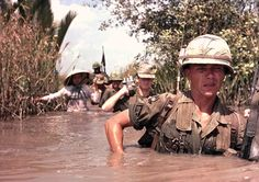 Members of the 199th Infantry Brigade move through a leach infested irrigation canal while participating in Operation Rang Dong near Cat Lai.