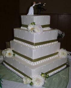 Bolo de casamento quadrado com noivos no topo, e flores brancas