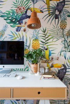 Home office tem papel de parede com estampa tropical e mesa de madeira clara.
