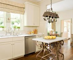 Understated Elegance. An elegant table functions as an eye-catching island in this traditional kitchen. A whimsical, distressed table base with a crisp marble countertop adds one-of-a-kind vintage character. A rustic chandelier above the island transforms the area into an instant focal point. :)
