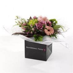 An expertly hand-tied bouquet of pink roses, pink gerbera, pink bouardia, shamrock, chrysanths, lime santini, alstromeria, cymbidium orchid blooms with seasonal foilage presented in exclusive Bumblebeez wrap and a black gift bag.