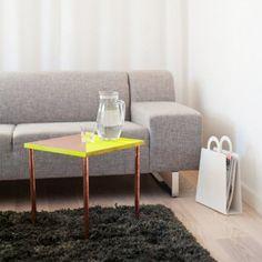 une table basse avec des pieds en tubes de cuivre