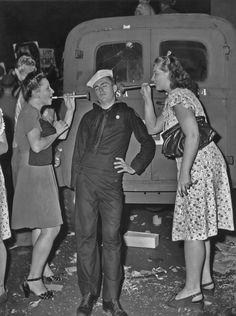Two women blow horns in to the ears of a sleepy sailor whilst celebrating VJ Day in New York in August 1945. (Photo by FPG/Getty Images)