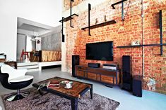 The homeowners enhanced the living room's industrial theme with a coffee table and TV console from Journey East.