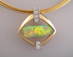 This spectacular pendant is centered around its awe-inspiring 3.8 carat hand-cut gem quality green-orange crystal opal sourced directly from Coober Pedy Australia. The opal is surrounded by 18 karat yellow gold and features .50 carat diamonds set in plati