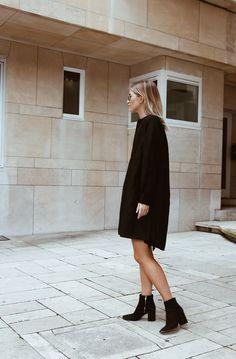 Simple black dress and boots for cloudy spring weather.