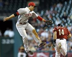 Cincinnati Reds First Baseman Joey Votto, Left, Reaches