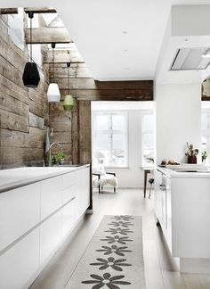 white kitchen with natural wood wall