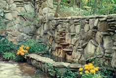 Rock wall build as fountain and pool in patio area in backyard