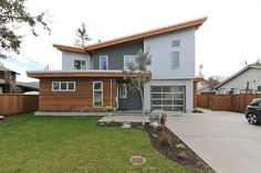 Corrugated metal, stucco and cedar siding. Light gray, dark gray, and cedar color scheme.