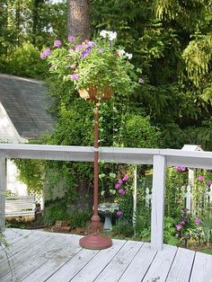 old wire egg basket and a thrift store floor lamp stand to make this outdoor flower stand. The basket is lined with black landscape cloth and a hanging basket liner.: