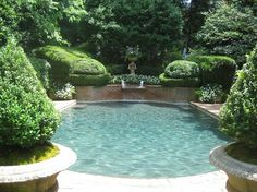 Adore this pool surrounded by carefully clipped and cared for shrubs and hedges - most especially love that brick wall with fountain. What a special hideaway. // Foo Dog strikes again. Lovely pool.