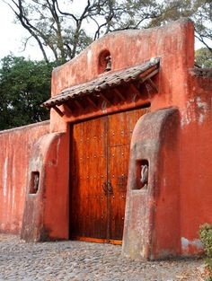 Adobe wall with buttresses.  Double wood doors with iron hardware.  Tejas roof.