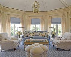 """Lovely blue and cream living room with cove ceiling elaborate moldings roman shades and sheers. Nice carpet color and design deep, soft chairs, interesting quatrefoil shape ottoman and ornate brass hanging """"lantern."""""""