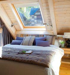 Dormitorio con techo abuhardillado y ventana tipo Velux sobre la cama