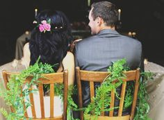 Rustic wedding decor. Love the green vine wrapped around chairs!