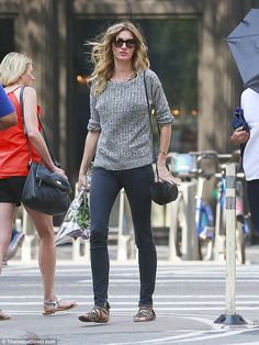 In a grey mood: The cover girl looked down on August 30 in New York as she carried with her purple roses