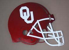 "Oklahoma Sooners Steel Football helmet crafted from 14 gauge finished steel with 3-d logo and facemask, measures 19"" (h) x  24"" (w) on Etsy, $125.00"