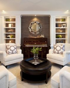 This is a perfect example of how contrasting color schemes can compliment each other while complimenting themselves. The rich, dark centerpiece compliments the dark trim of the backsplash and shelves. The white couches, floors and shelve framework compliment each other as well. The combination of color schemes gives a great uniformity to the room without taking away from the distinctive feel of elegance.