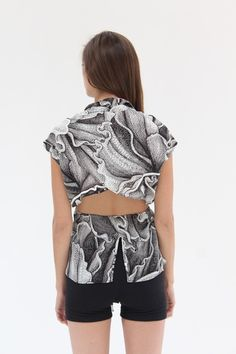 100% silk blouse with black and white hand drawn floral print, drawstring tie waist, open back detail and uneven hem. Model is wearing size small. Made in USA.