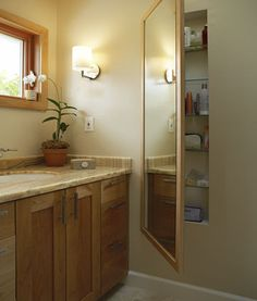 Carve out storage space between wall studs and use a mirror as a door.