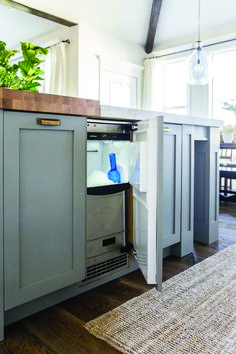 A stainless steel ice maker is concealed behind a cabinet door of a gray blue kitchen island accented with antique brass cup pulls and butcher block top and white quartz countertop. Kitchen Maker, Huge Kitchen, Kitchen Redo, Kitchen Remodel, Mini Kitchen, Kitchen Countertops, Kitchen Cabinets, Gray Cabinets, Blue Kitchen Island