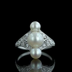 Three luminous natural pearls form the focal point of this engraved, pierced and millgrained platinum ring with single, European and round diamonds glittering within the scroll work. The center natural 3/4 pearl measures 7.8 mm and the other round pearls measure 5.5 mm and 5.7 mm.
