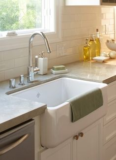 A concrete counter top, farmhouse sink and subway tile with white cabinets.