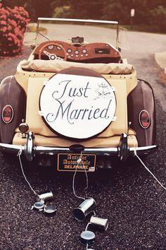 Antique brown car with a just married sign with tin cans from antique automotive in delaware.