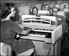 Organist Nan Bergin plays for luxury-class pax aboard NWA LGA-MDW-MSP flight, Nov. 1959.