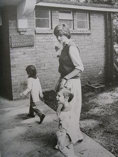 Diana, posing for photographers with two of her charges from the All England Kindergarten, 1980