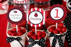White cups decorated with ribbon and filled with red candy for a lady bug party