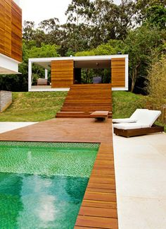 Separate modules of shipping container  surrounding an infinity pool -- design by phases