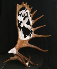 Hand carved Moose Antler carving depicting 2 eagles fighting over a salmon.