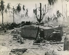 Two GIs rest next to a bunker on Kwajalein.