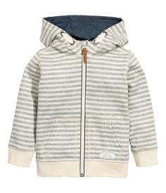 Sweatshirt jacket with a lined hood. Zip at front, side pockets, and ribbing at cuffs and hem.