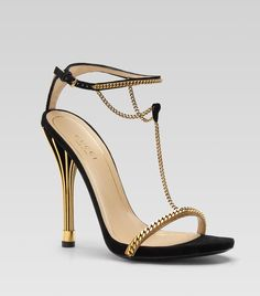 Gucci 'Ophelie' t-strap high heel sandals featuring black suede and gold color leather trim, antique gold metal chain detail, ankle strap with buckle closure and a leather sole on a 4.5 inch heel