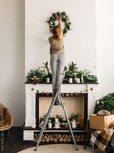 Young ginger woman decorating Christmas Interior during the day