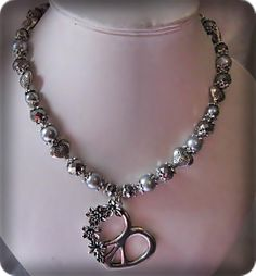 Necklace made of grey glassbeads, crystal beads, metal caps and spacers, and a tibetan heart