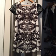 TOBI print shift Flattering tobi print dress. Faux leather sleeves with a slight curve at side hem( pictured ). Hits an inch above the knee. Slim fit. True to size XS. Never worn  Tobi Dresses