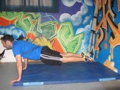 Flexiones de brazos con TRX: manos apoyadas en el suelo un poco más atrás de los hombros. Pies sobre el TRX. Flexionar los codos hasta casi tocar el suelo con el pecho y volver a estirar. Tip: cuerpo recto como una tabla.
