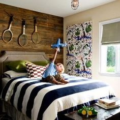 love the antique tennis racquets hung on the old barnboard wall...and the navy striped duvet!