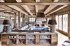 Salon du chalet : canapé et cheminée centrale, lampes abat-jour, poutres apparentes
