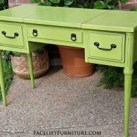 Vanity desk in distressed Lime Green with Black Glaze. Two side drawers, with top opening over middle compartment. Original pulls painted black. From Facelift Furniture's Desk & Vanities collection.
