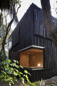 Herbst Architects is an award winning New Zealand based Architecture firm. The design of this Piha, New Zealand beach house takes inspiration from its coastal scenery and Pohutukawa trees surrounding it. New Zealand Architecture, Architecture Résidentielle, Architecture Durable, Sustainable Architecture, Wooden Cladding, Black Cladding, New Zealand Beach, Contemporary Beach House, Design Exterior
